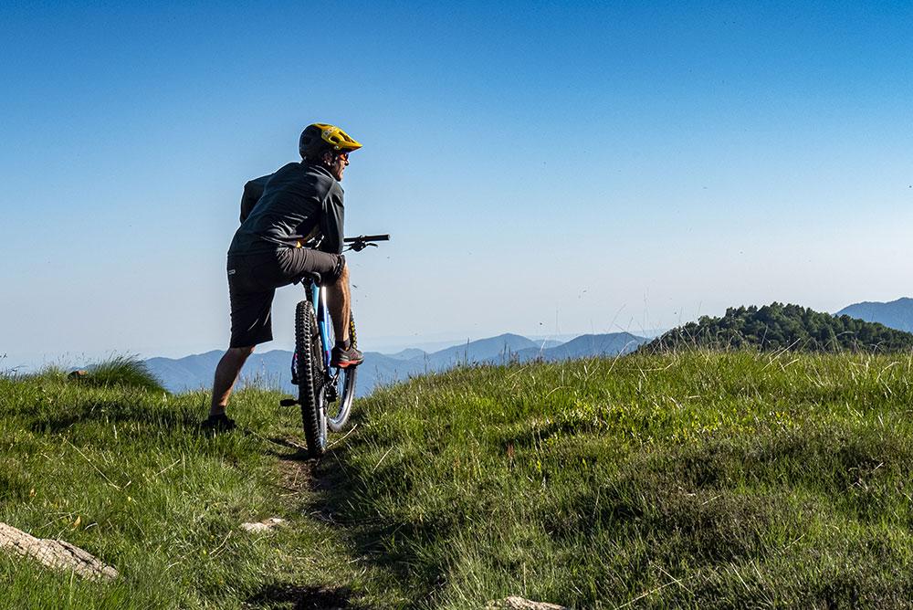 foto-di-un-uomo-appoggiato-su-una-bici-elettrica-in-montagna