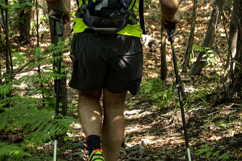 persona-che-cammina-su-un-sentiero-di-montagna-vestita-da-trekking