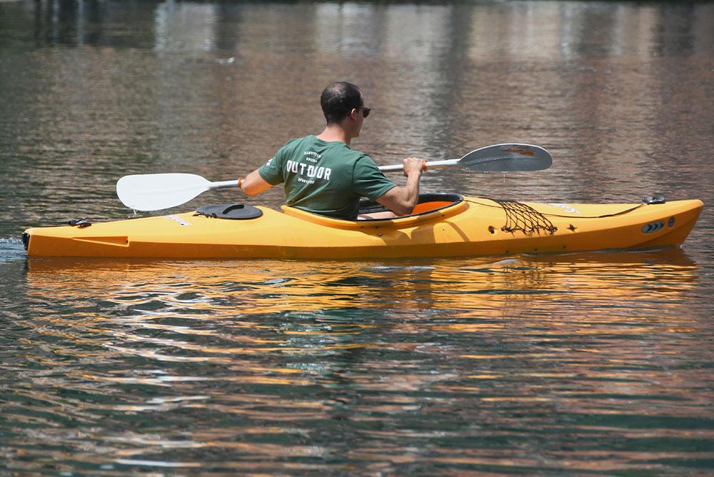 primo-piano-di-un-uomo-ripreso-di-schiena-che-va-su-una-canoa-gialla