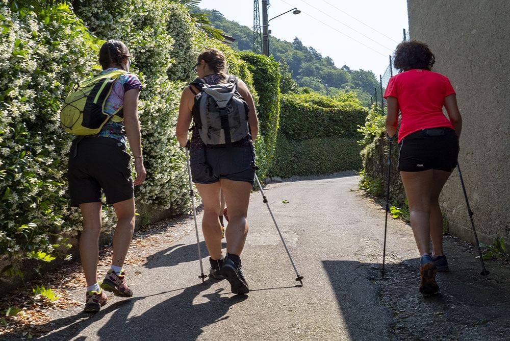 tre-persone-vestite-da-trekking-che-camminano-su-una-strada-asfaltata